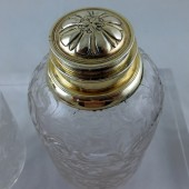 Pair of cut glass bottles with silver gilt tops